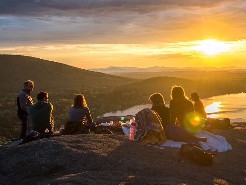 Group of adults haivng a picnic on top of a mountain. The sun is setting over a lake in the background.