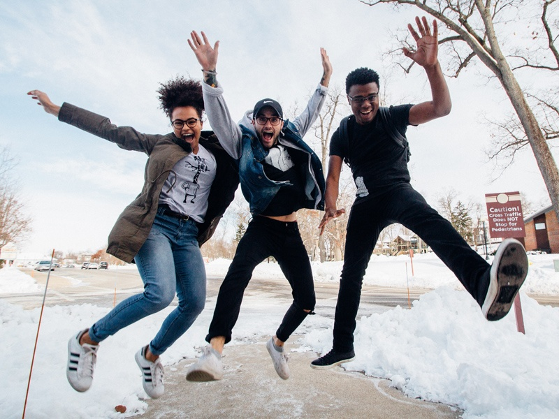 Three teenagers jumping on a sidewalk with snow on the ground